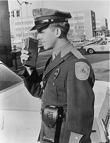 Officer uses a walkie-talkie in 1966