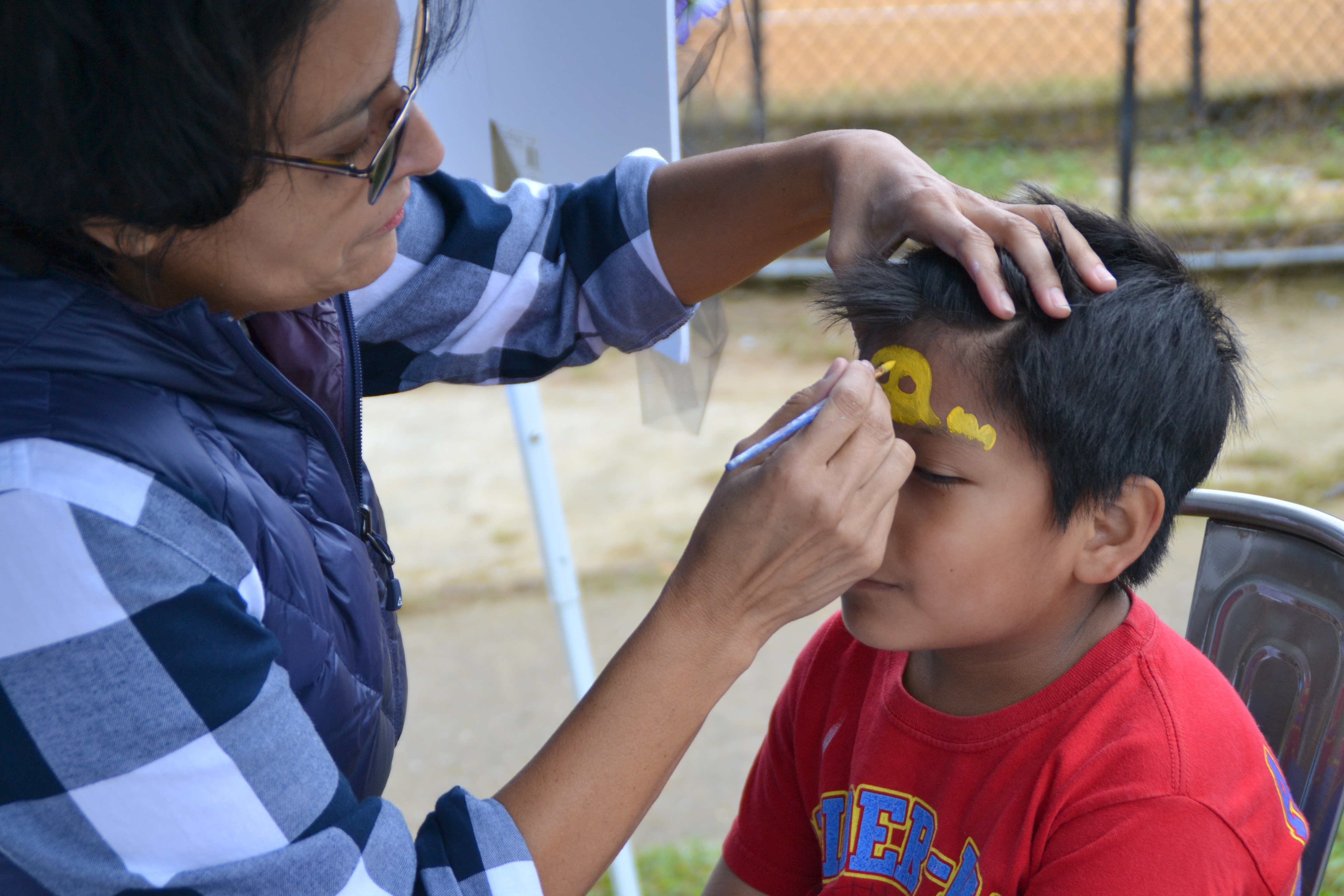 Volunteer face painting at Imagine Festival