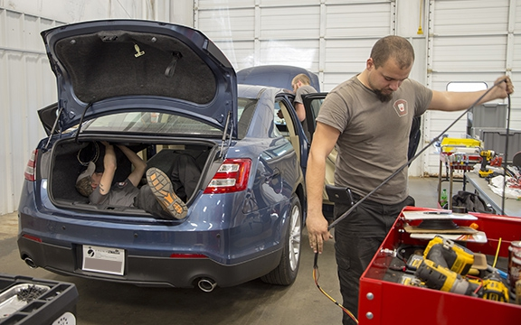 Staff installing equipment in detective car