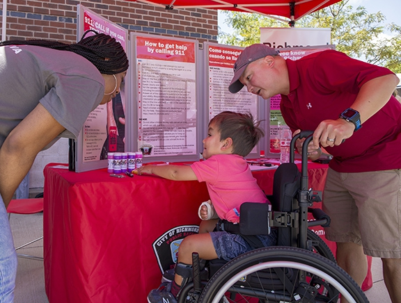 Boy in wheelchair selects prize from DEC booth at 2018 event