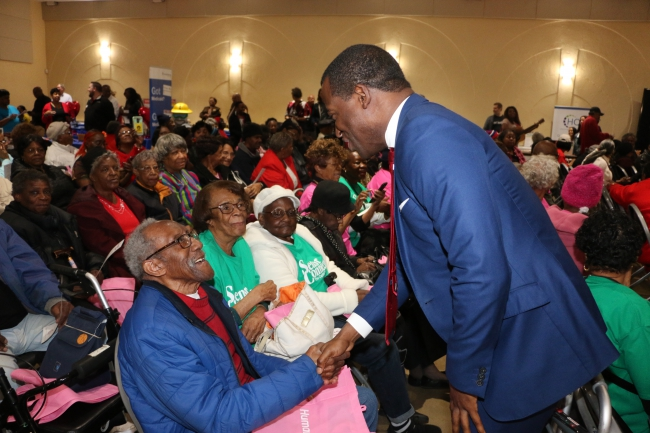 Mayor Stoney shakes the hand of a centenarian.